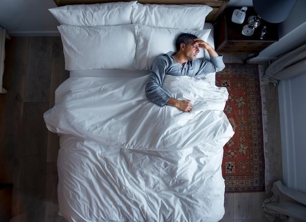 Homem, cama, dor de cabeça Foto Premium