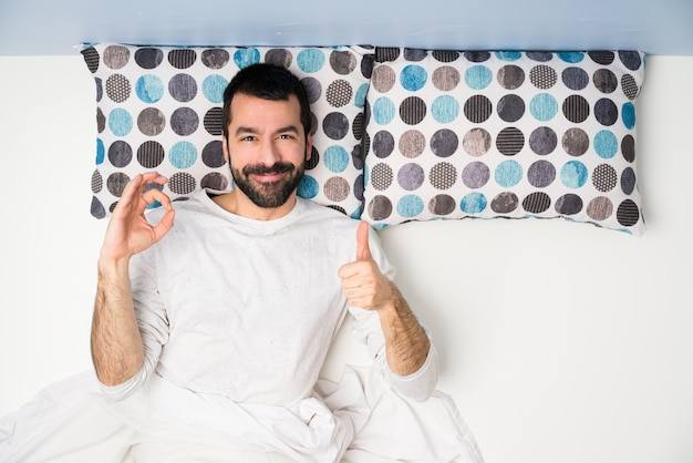 Homem, cama, em, vista superior, mostrando, tá bom sinal, e, polegar cima, gesto Foto Premium
