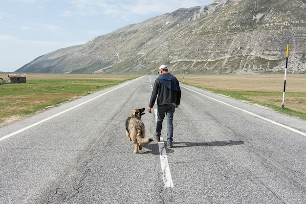 Homem caminhando na estrada com seu cachorro nas montanhas Foto Premium
