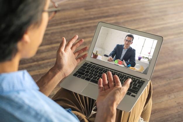 Homem, candidatando-se a um trabalho remoto. ele está fazendo sua entrevista em uma vídeo chamada. Foto Premium