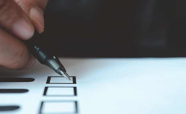 Homem, caneta segurando, marcar, voto, papel Foto Premium