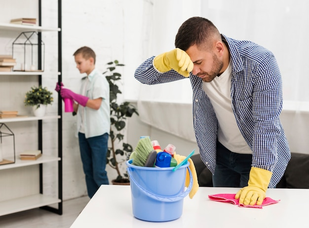 Homem cansado depois de limpar a casa Foto gratuita