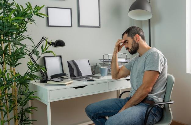 Homem cansado sentado em sua mesa de casa Foto gratuita