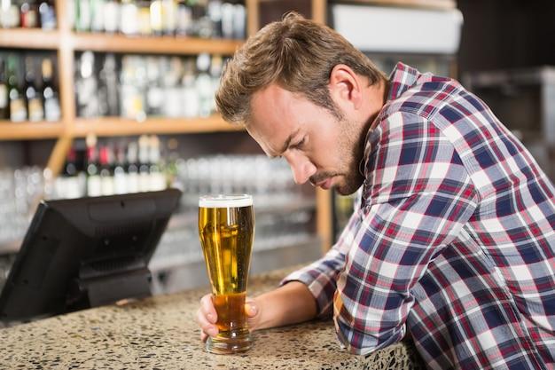 Homem cansado, tomando uma cerveja Foto Premium