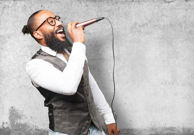 Homem cantando através de um microfone Foto gratuita