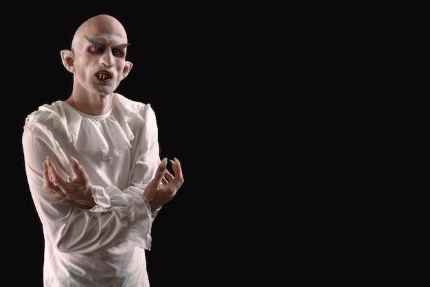 Homem caracterizado como vampiro em um fundo preto. Foto Premium