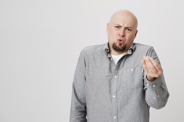 Homem careca irritado descontente julgando ou reclamando Foto gratuita