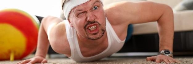 Homem careta engraçado fazendo flexões em casa durante o retrato de período de quarentena de coronavírus Foto Premium