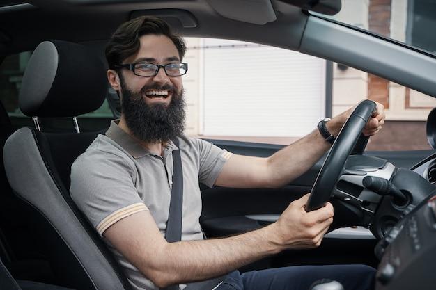 Homem carismático feliz dirigindo um carro Foto gratuita