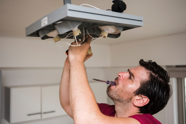 Homem, carregar, tester, em, boca, enquanto, reparar, teto, foco, luz, casa Foto gratuita