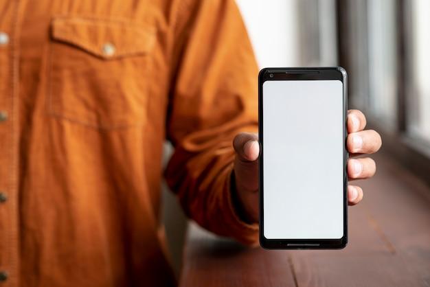 Homem casual, mostrando seu telefone celular Foto gratuita