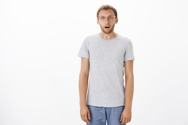 Homem caucasiano atraente e engraçado e atordoado com cerdas nos óculos, queixo caído, olhando trêmulo e surpreso em pé como uma marionete sobre a parede branca Foto gratuita
