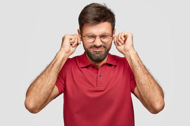 Homem caucasiano barbudo estressante tapando os ouvidos com os dedos, mantendo os olhos fechados Foto gratuita