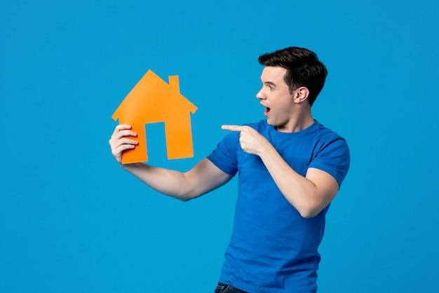 Homem caucasiano bonito animado segurando e apontando para o modelo de casa Foto Premium