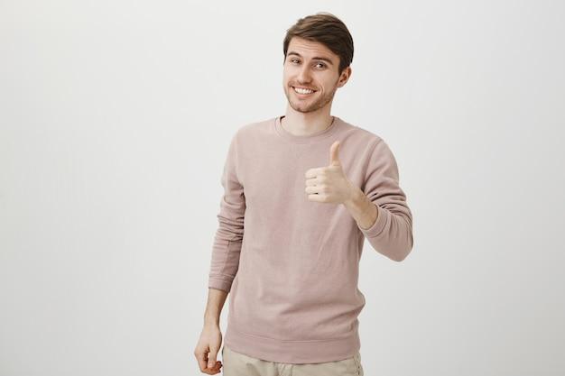 Homem caucasiano bonito satisfeito mostrando o polegar para cima Foto gratuita