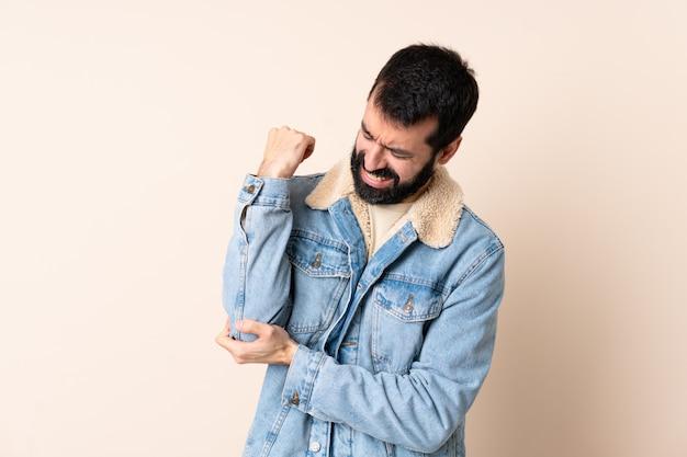 Homem caucasiano com barba isolado com dor no cotovelo Foto Premium
