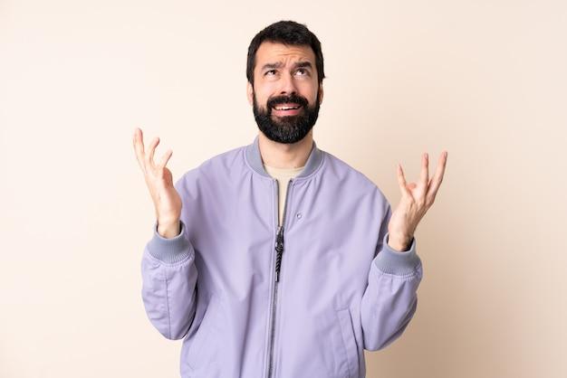 Homem caucasiano com barba, vestindo uma jaqueta sobre isolado estressado oprimido Foto Premium