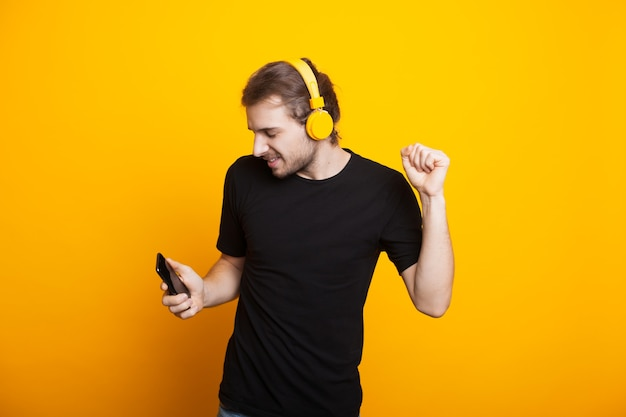 Homem caucasiano com cabelo comprido e barba dançando com fones de ouvido na parede amarela segurando o telefone Foto Premium