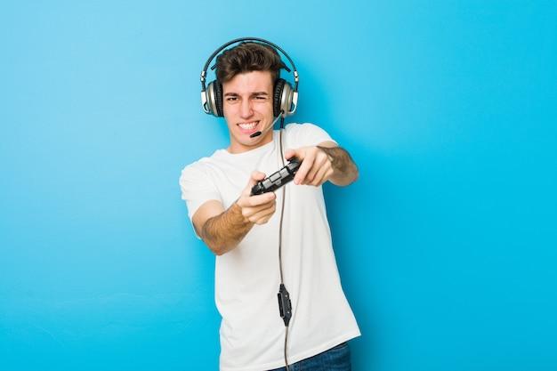 Homem caucasiano de adolescente usando fones de ouvido e controlador de jogo Foto Premium