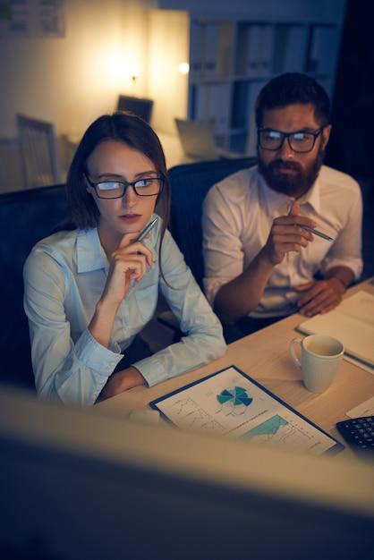 Homem caucasiano e mulher trabalhando juntos no escritório na noite Foto gratuita