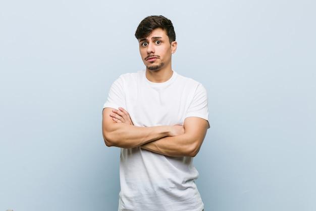 Homem caucasiano novo que veste uma vista infeliz do tshirt branco com expressão sarcástica. Foto Premium
