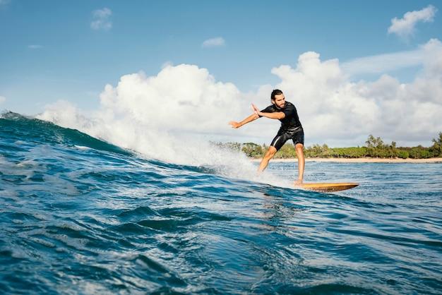 Homem cavalgando sua prancha de surfe e se divertindo, tiro longo Foto gratuita