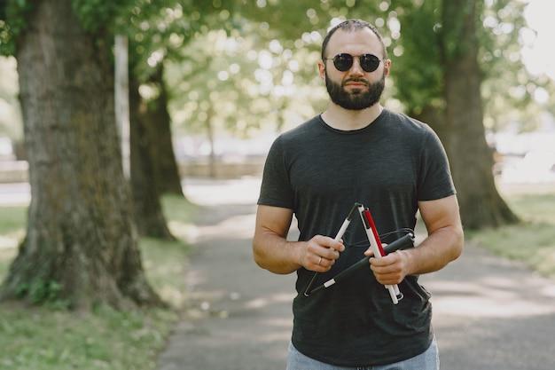Homem cego. pessoas com deficiência, pessoa com deficiência e o dia a dia. homem com deficiência visual com bengala, descendo degraus no parque da cidade. Foto gratuita