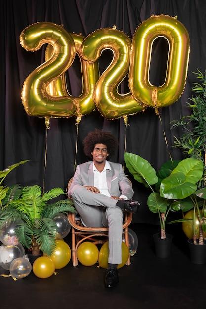 Homem cercado por feliz ano novo 2020 balões de ouro Foto gratuita