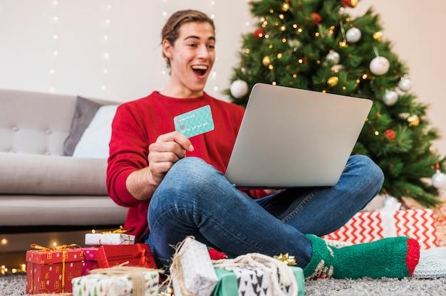 Homem chocado com cartão de crédito e laptop Foto gratuita