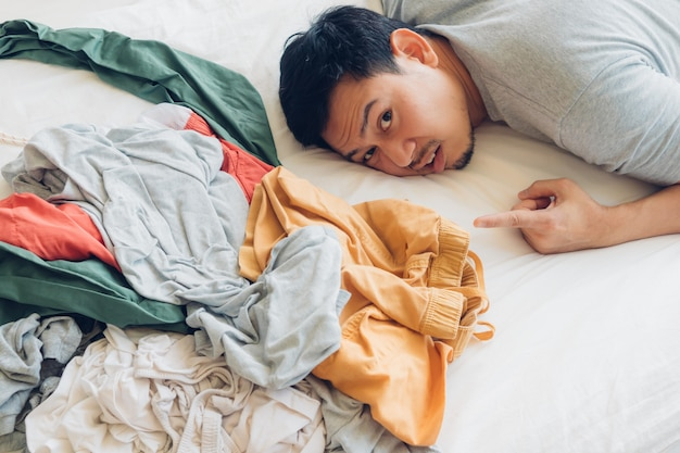 Homem chocado e triste que tem que cuidar de toda a pilha de roupas. Foto Premium