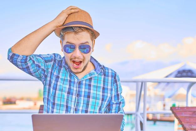 Homem chocado na camisa e chapéu em dia de sol no cais à beira-mar, surpreso por algo Foto Premium