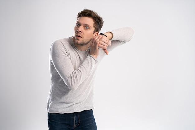 Homem chocado olhando no relógio de pulso, sobre fundo branco. Foto Premium