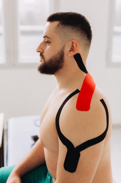Homem close-up, levantando os braços. esportista com fita de kinesio no ombro e braço após lesão de treino no ginásio. Foto Premium