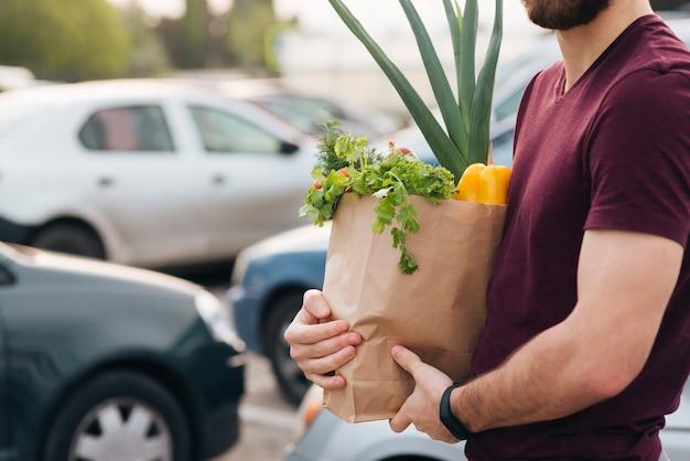 Homem close-up, segurando, saco, com, mantimentos Foto gratuita