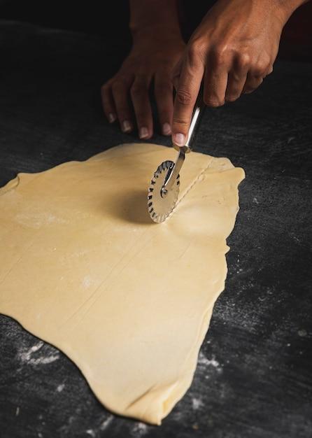 Homem close-up, usando, cortador pizza Foto gratuita