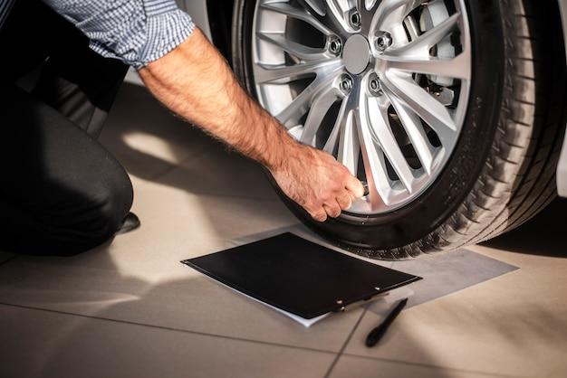 Homem close-up, verificação de pneus de carro Foto gratuita
