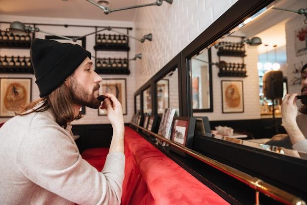 Homem coçando a barba perto do espelho Foto gratuita