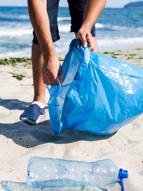 Homem coletando lixo plástico da praia e colocá-lo em sacos de lixo azuis para reciclagem Foto gratuita
