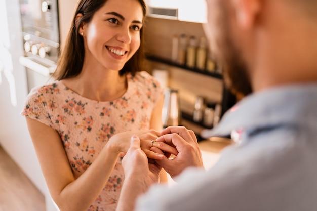 Homem coloca o anel no dedo de suas namoradas Foto gratuita
