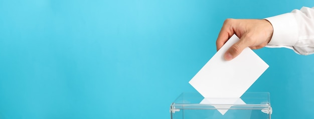Homem colocando cédula na urna na superfície azul Foto Premium