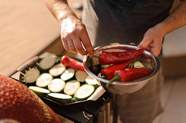 Homem colocando grandes pimentas vermelhas para as berinjelas na grelha Foto Premium