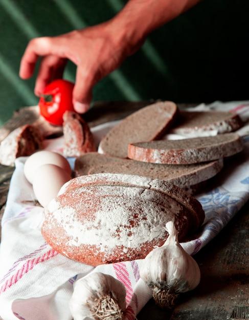 Homem colocando tomate numa toalha de mesa branca com fatias de pão, ovos e alho luvas ao redor. Foto gratuita