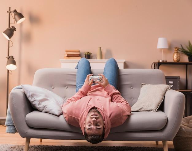 Homem com a cabeça de cabeça para baixo, jogando o jogo Foto gratuita