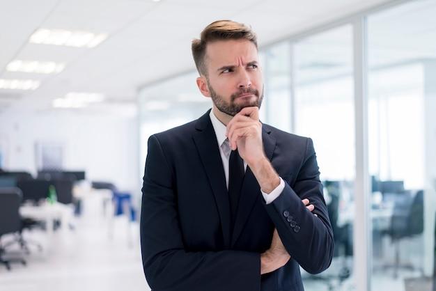 Homem com a mão no queixo pensando Foto Premium