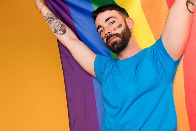 Homem com arco-íris lgbt no rosto com bandeira multicolorida Foto gratuita