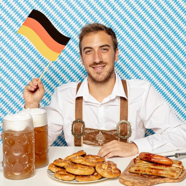 Homem com bandeira alemã, comida e cerveja Foto gratuita