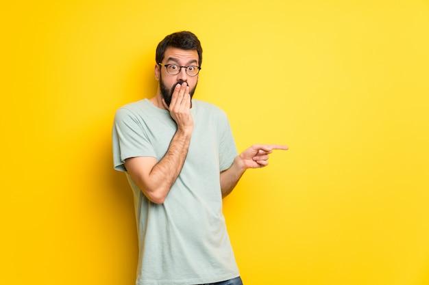 Homem, com, barba, e, camisa verde, apontar dedo, para, a, lado, com, um, surpreendido, rosto Foto Premium