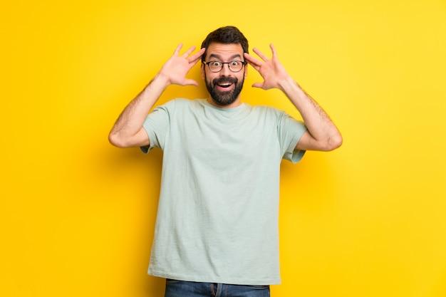 Homem com barba e camisa verde com surpresa e expressão facial chocada Foto Premium