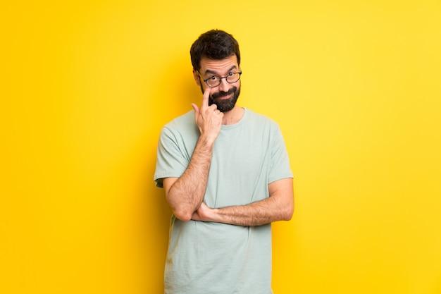 Homem com barba e camisa verde olhando para a frente Foto Premium