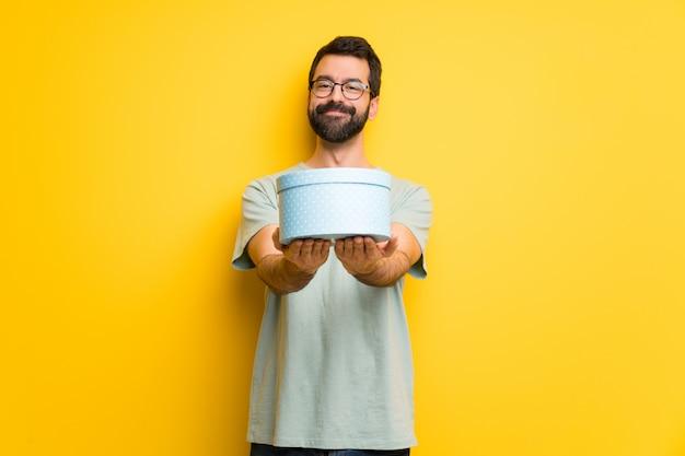 Homem, com, barba, e, camisa verde, segurando, um, presente, em, mãos Foto Premium